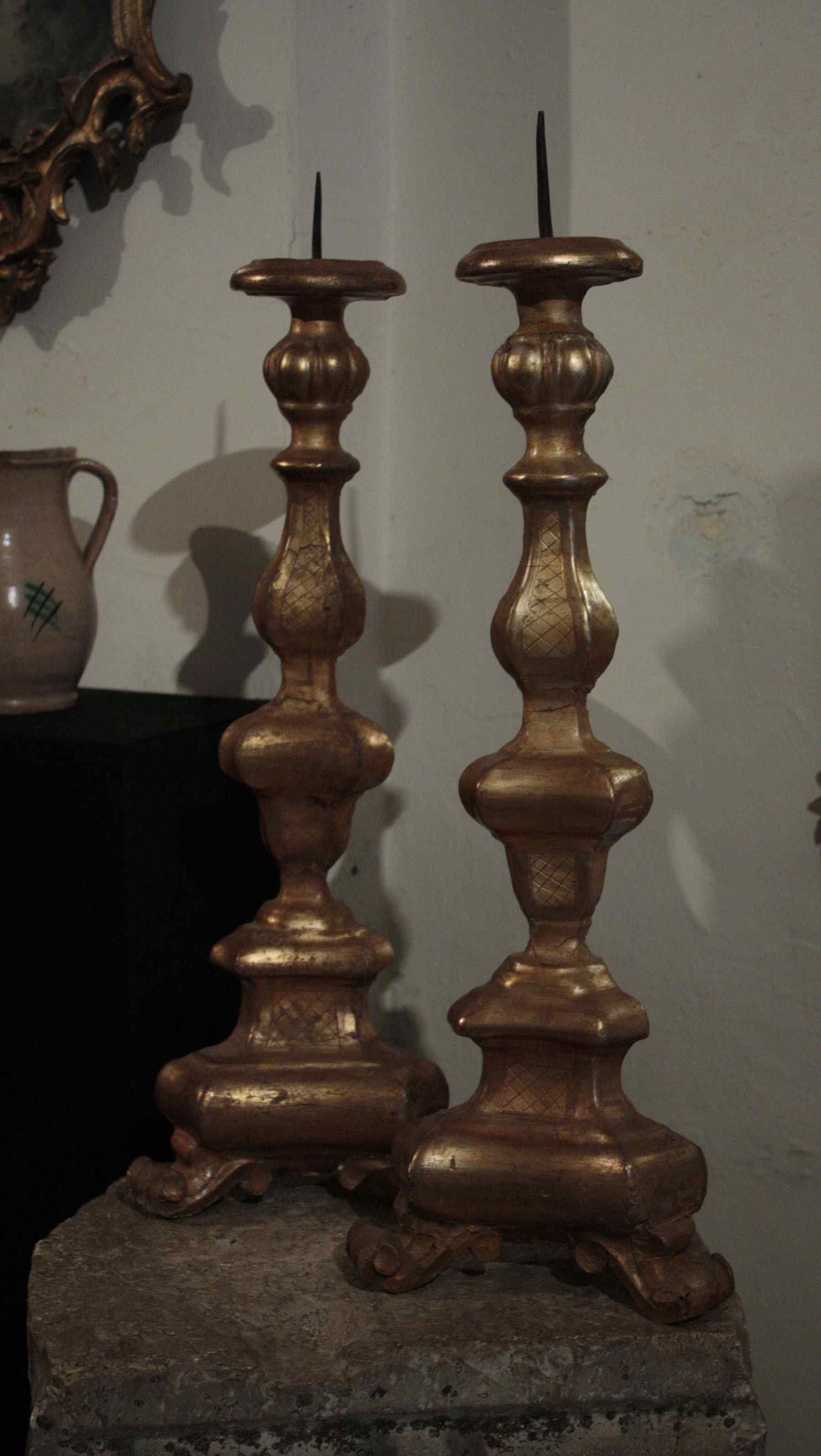 A pair of golden wooden candlesticks